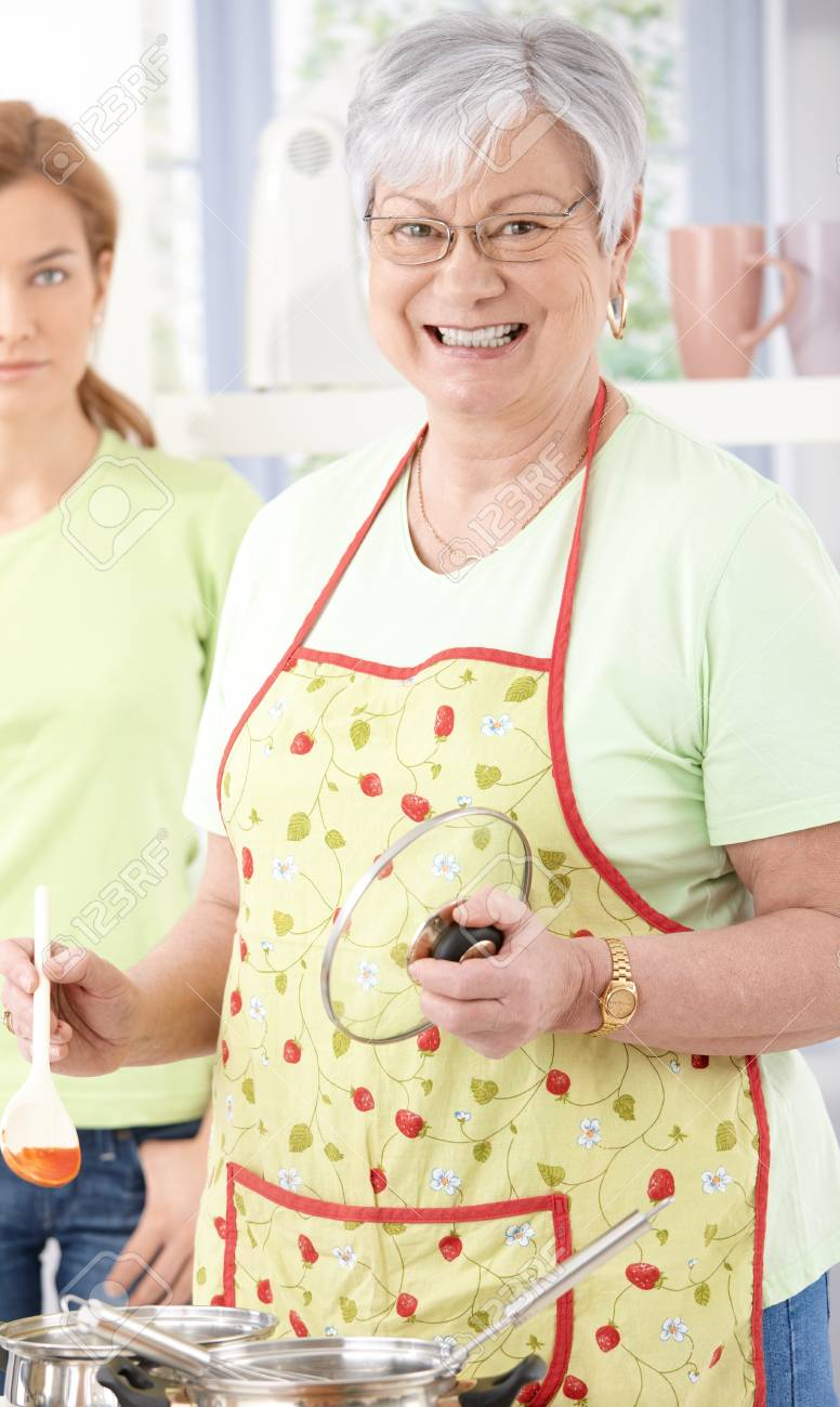 Senior woman cooking in kitchen, smiling happily, daughter standing at background. Stock Photo - 9208691