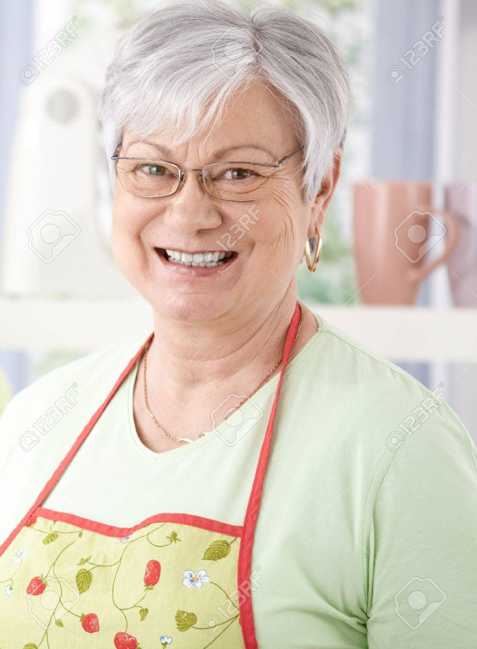Portrait of senior woman smiling happily, wearing cooking apron. Stock Photo - 9208600