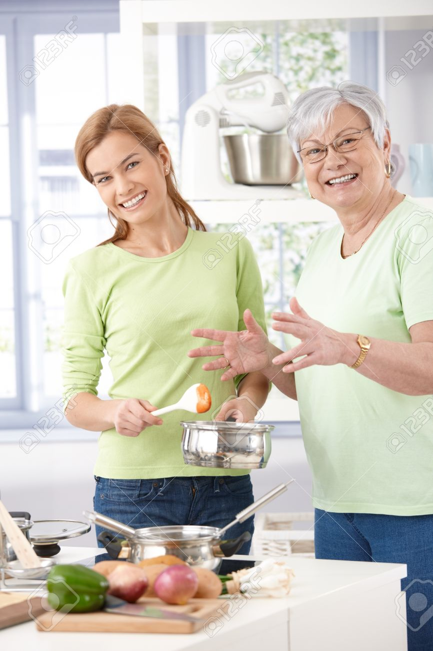 Senior mother and daughter cooking together, smiling, looking at camera. Stock Photo - 9209260
