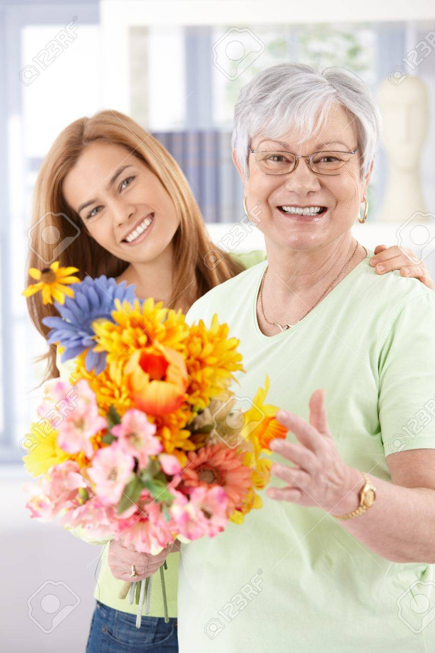 Happy senior mother and daughter smiling at mother's day, holding flowers. Stock Photo - 9208602