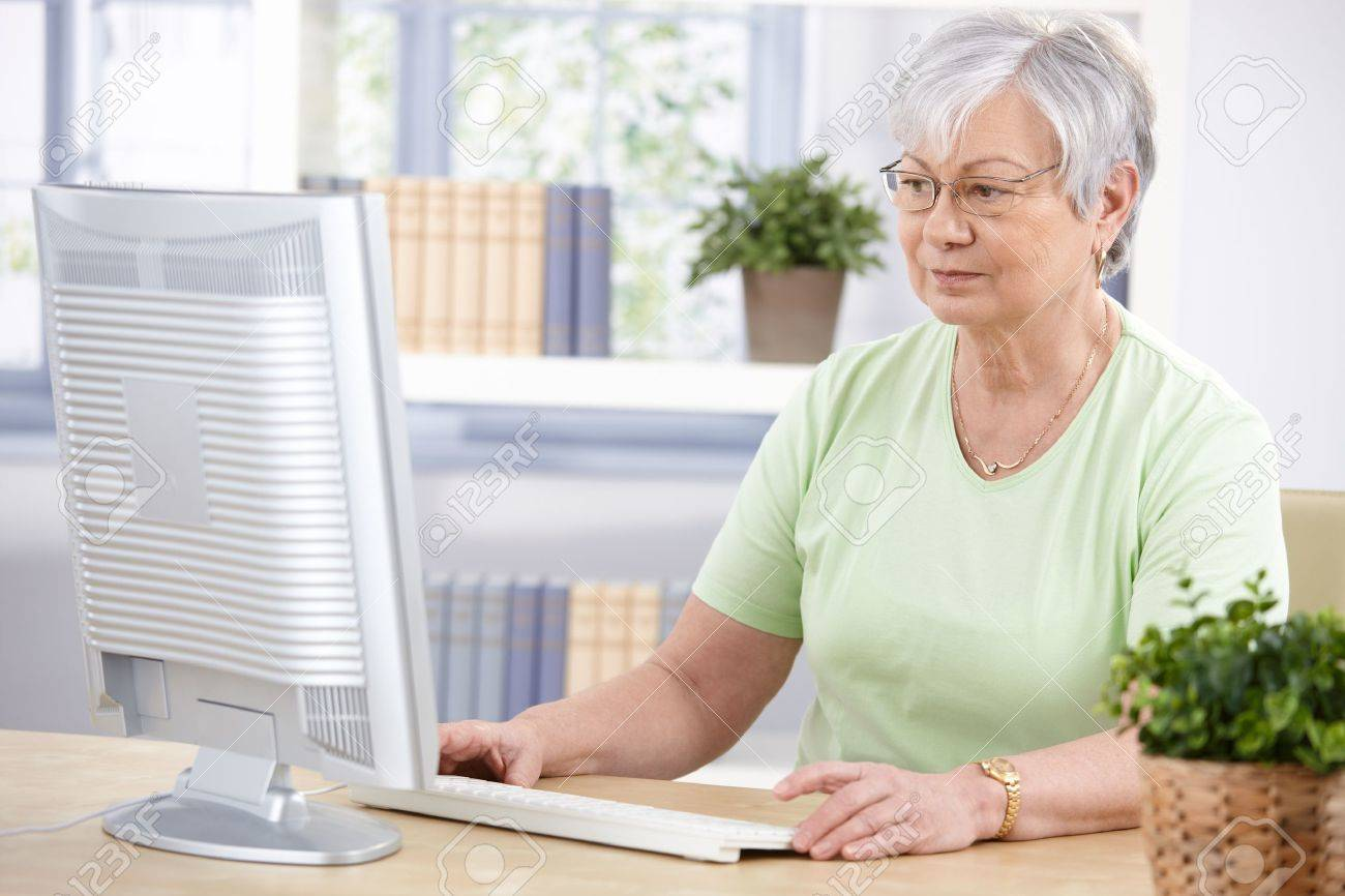 Senior woman sitting at desk, using computer at home. Stock Photo - 9208736