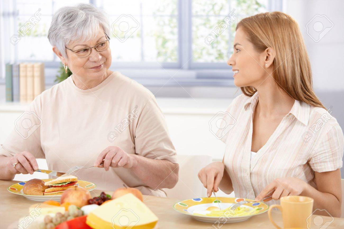 Young woman having lunch with her mother, talking, smiling. - 9208751
