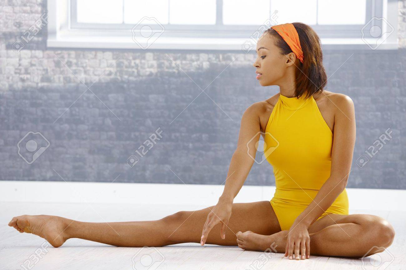 Ballet dancer concentrating on stretching on floor of art training room. Stock Photo - 9249553