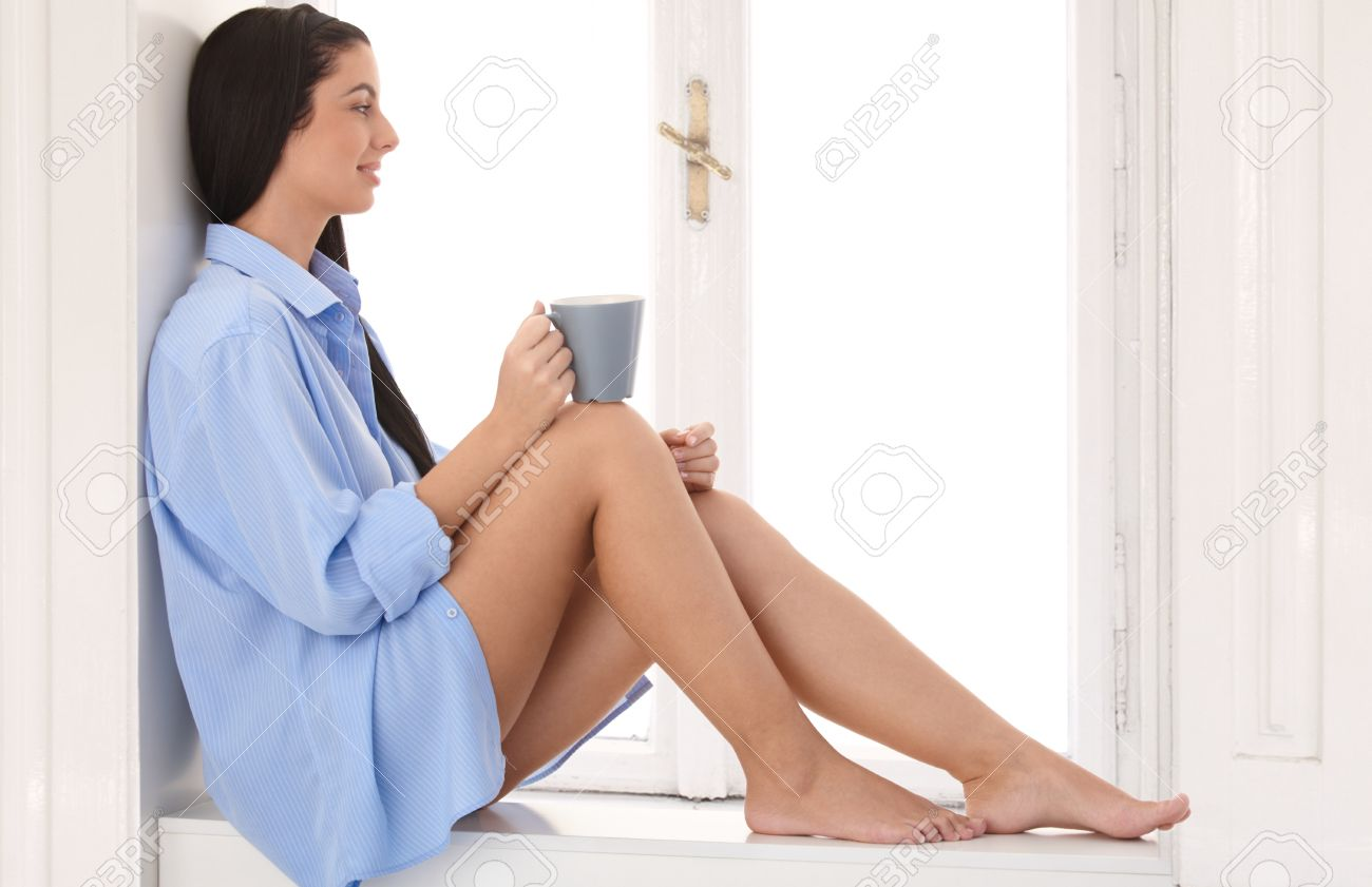 Daydreaming woman wearing only shirt sitting at window sill, drinking morning coffee, smiling. Stock Photo - 9298963