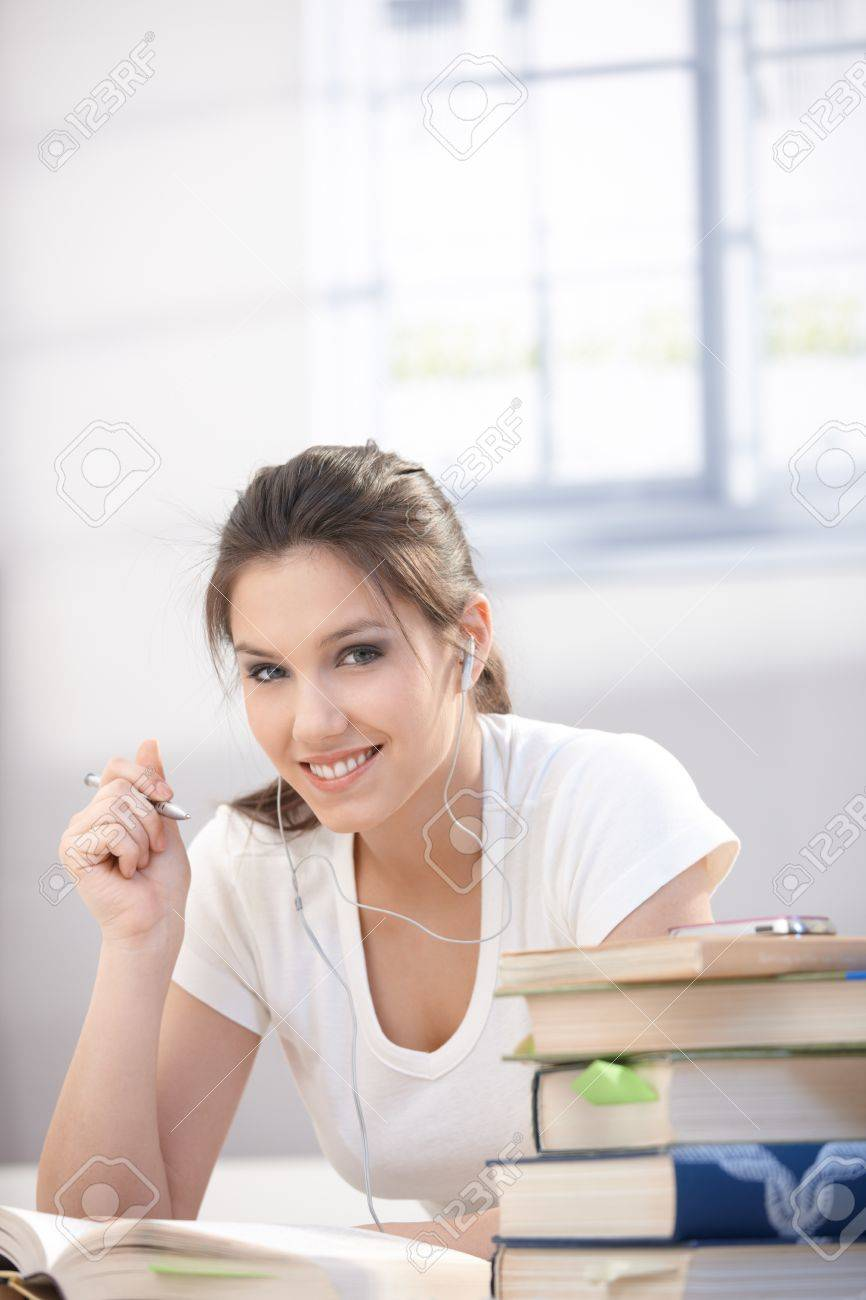 Pretty college student laying on floor, listening music, studying, smiling. Stock Photo - 9298982