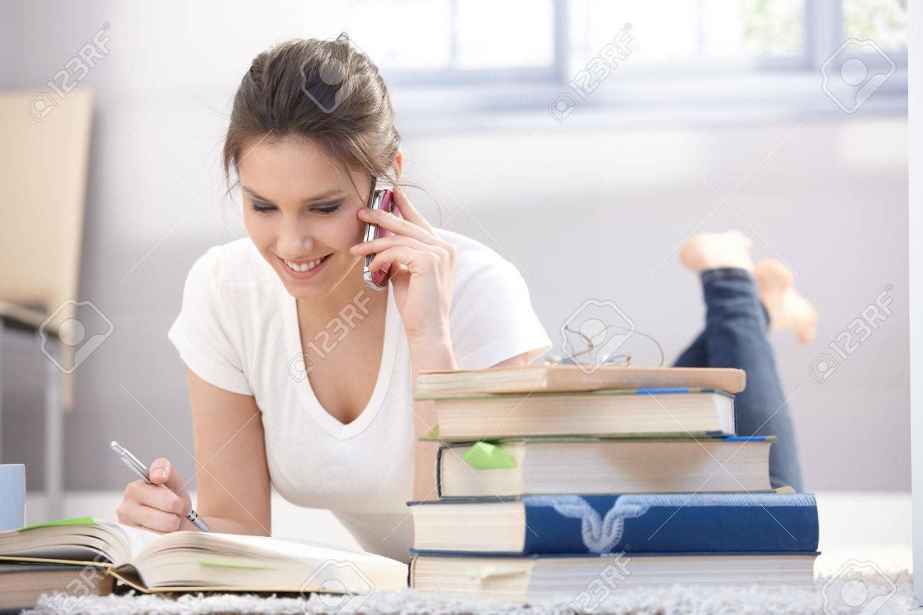 Pretty schoolgirl laying on floor, studying, chatting on mobile phone, smiling. Stock Photo - 9298995
