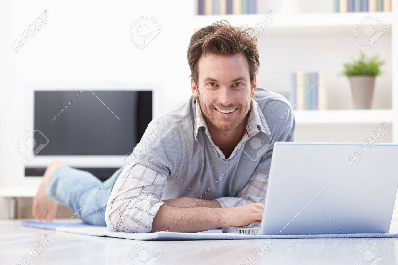 Casual young man laying on floor at home, browsing internet, smiling. Stock Photo - 9434889
