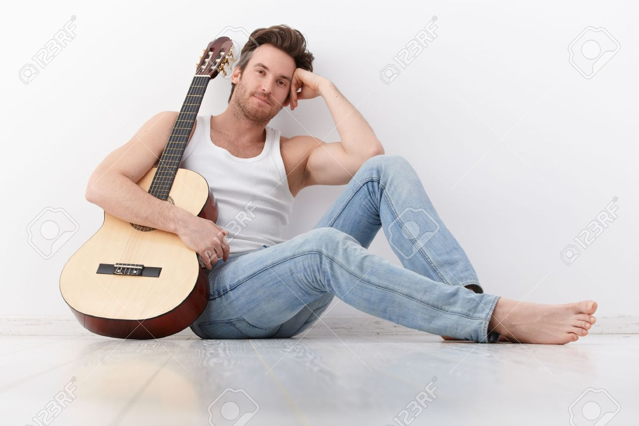 Goodlooking young man sitting by wall, holding guitar, smiling. Stock Photo - 9435178