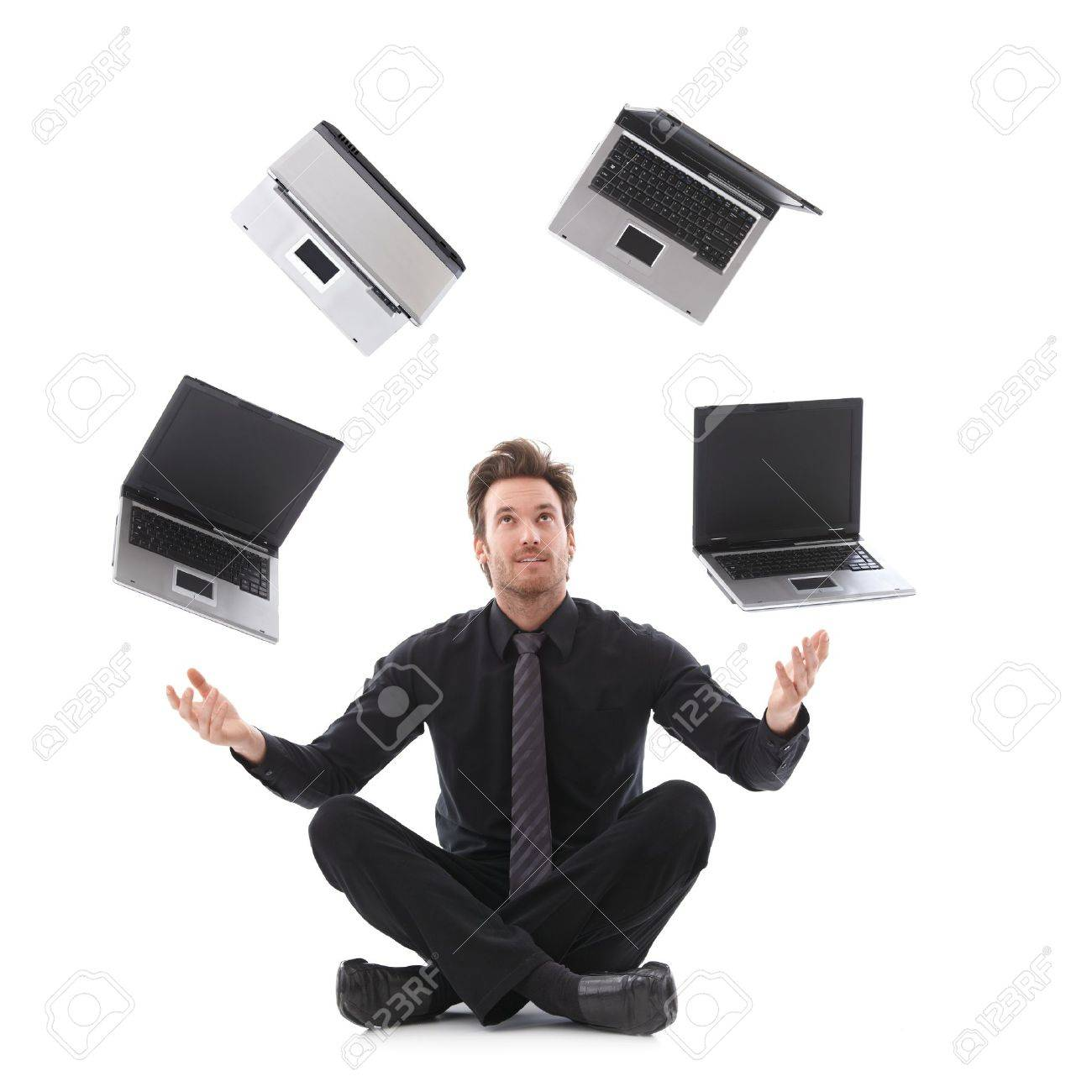 Handsome businessman in tailor seat juggling with laptops. Stock Photo - 9434672