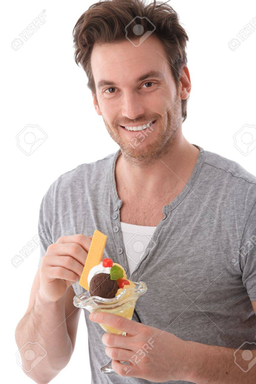 Portrait of handsome young man eating ice cream, smiling. Stock Photo - 9435070