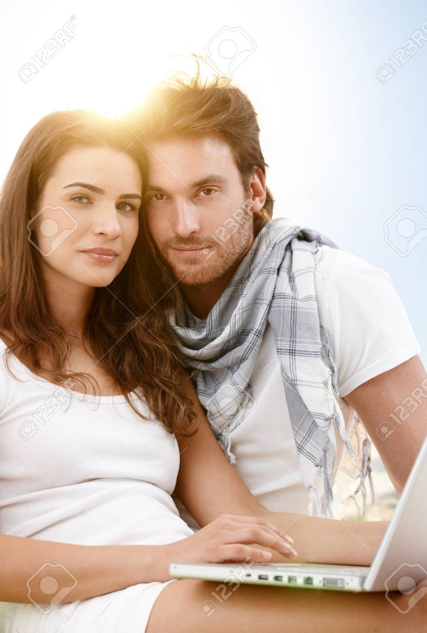 Attractive young couple sitting on the beach using laptop computer outdoor in summer sunlight, looking at camera, smiling. Stock Photo - 9434884