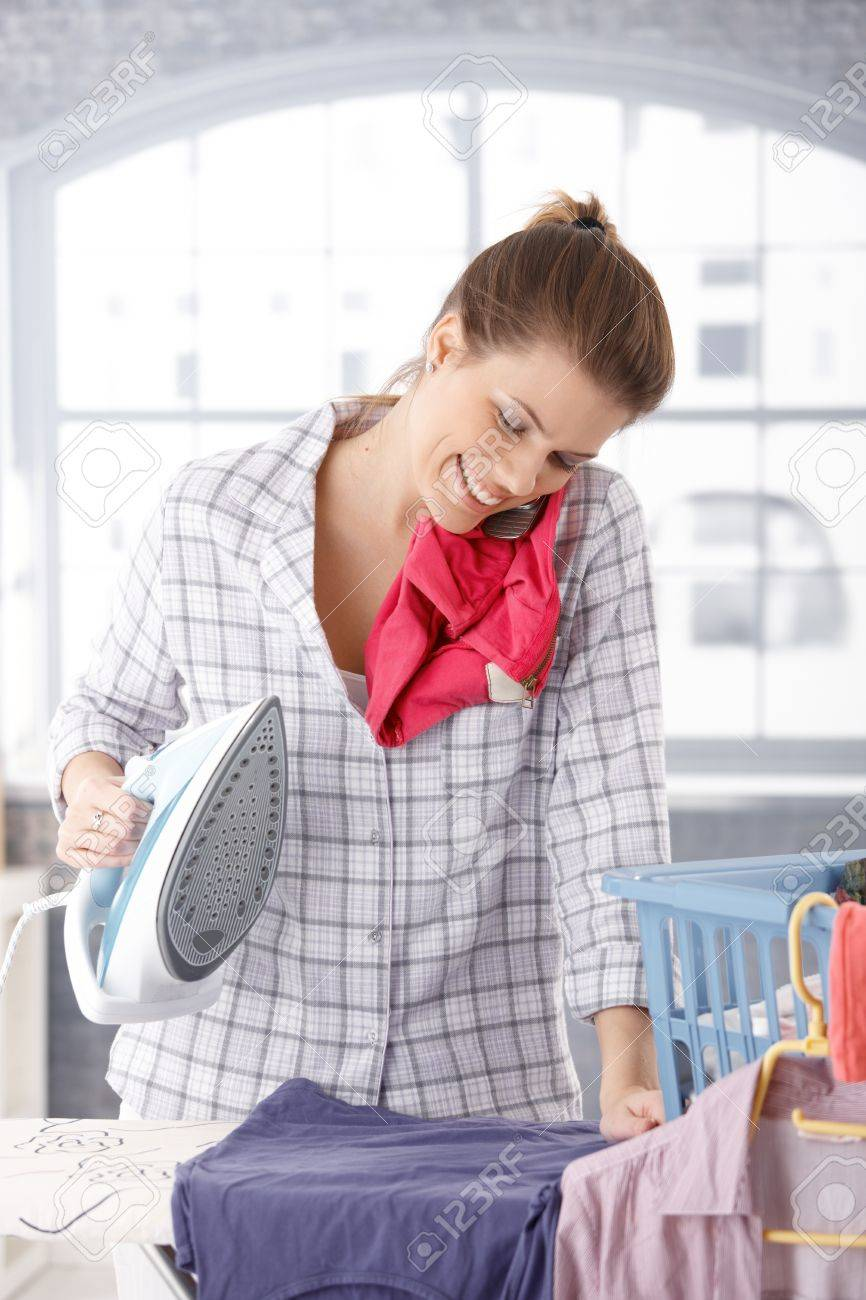 Happy woman talking on mobile phone while ironing clothes at home. Stock Photo - 9435316