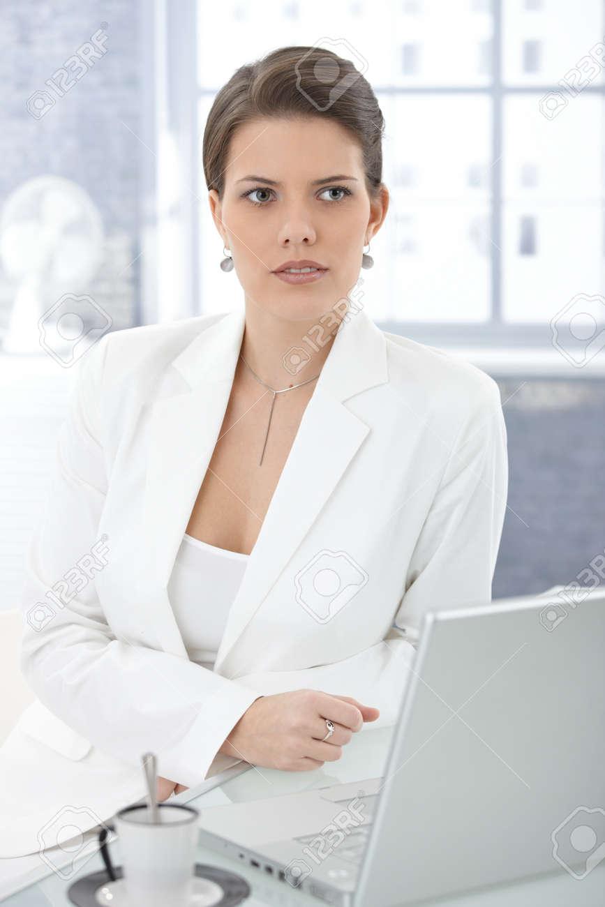 Elegant businesswoman sitting at desk, using laptop computer, thinking. Stock Photo - 9434789