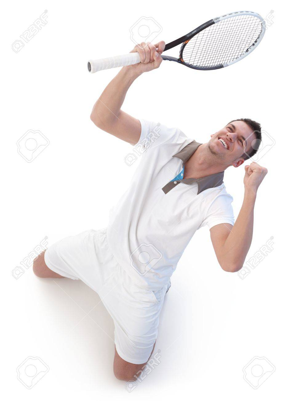 Young tennis player happy for victory, kneeling, looking up to the sky. Stock Photo - 9537989