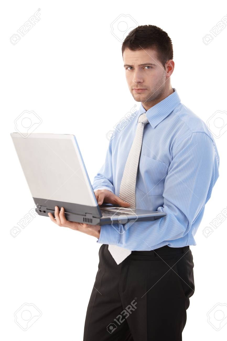 Goodlooking young businessman working on laptop, standing over white background. Stock Photo - 9538067