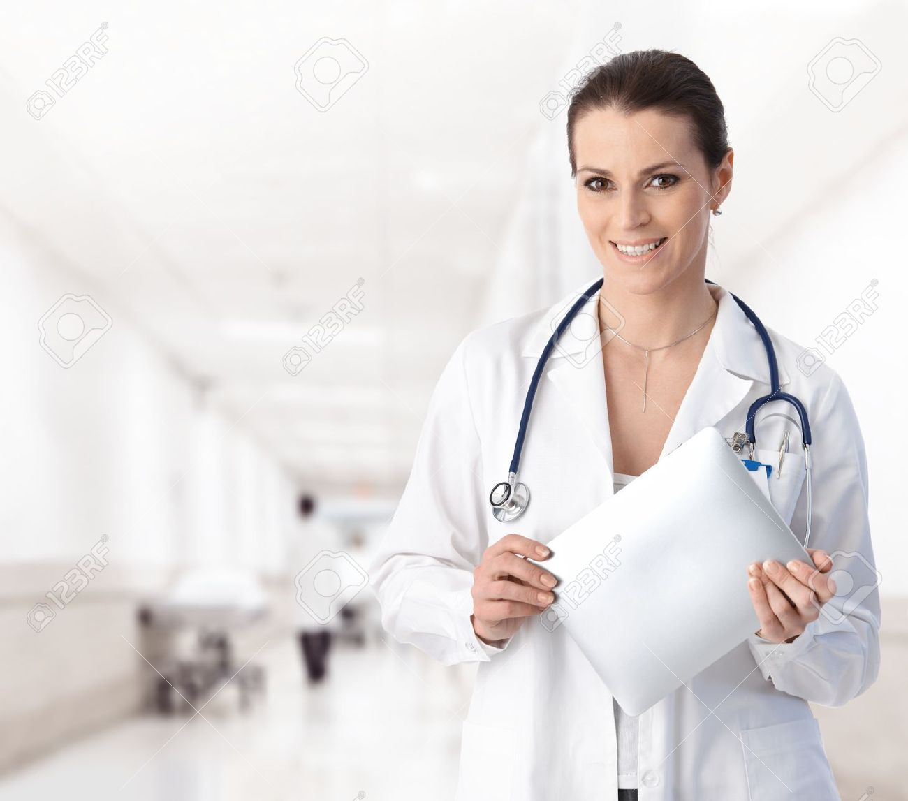 Portrait of woman doctor at hospital corridor, holding tablet computer, looking at camera, smiling.� Stock Photo - 9611561