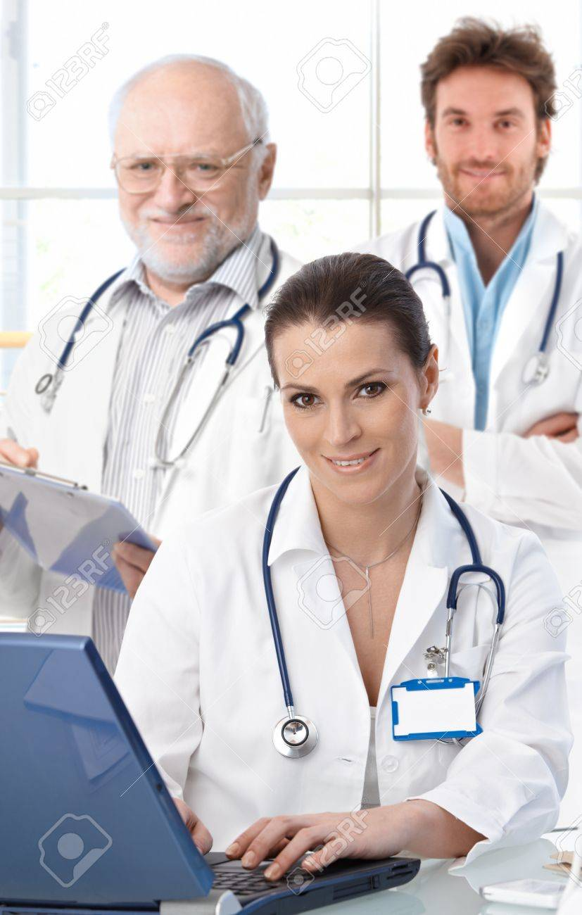 Doctors working at desk, female doctor in front, looking at camera, smiling.� Stock Photo - 9611558