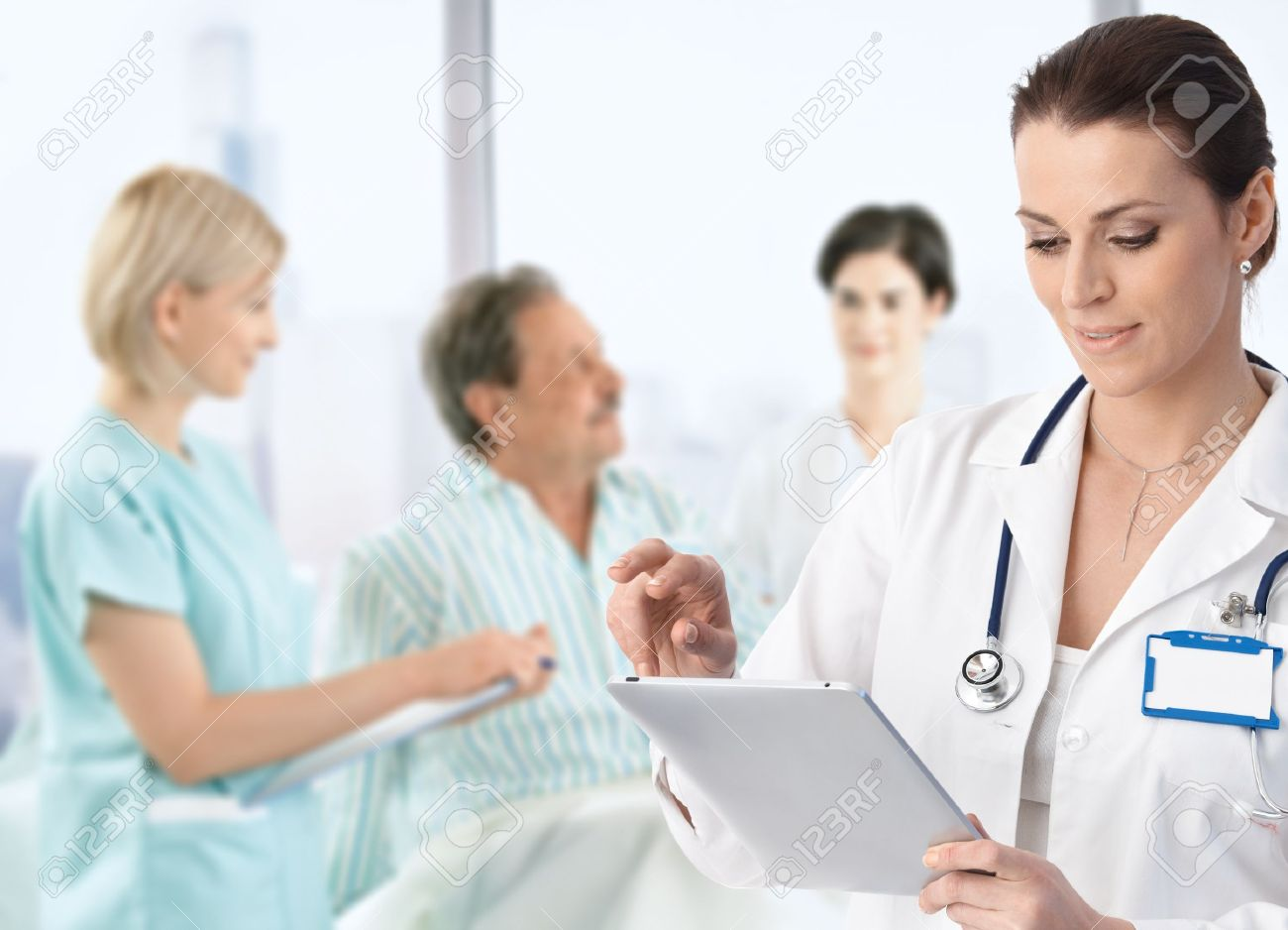 Doctor recording information to electronic tablet at patients bed, team working in background.� Stock Photo - 9611556