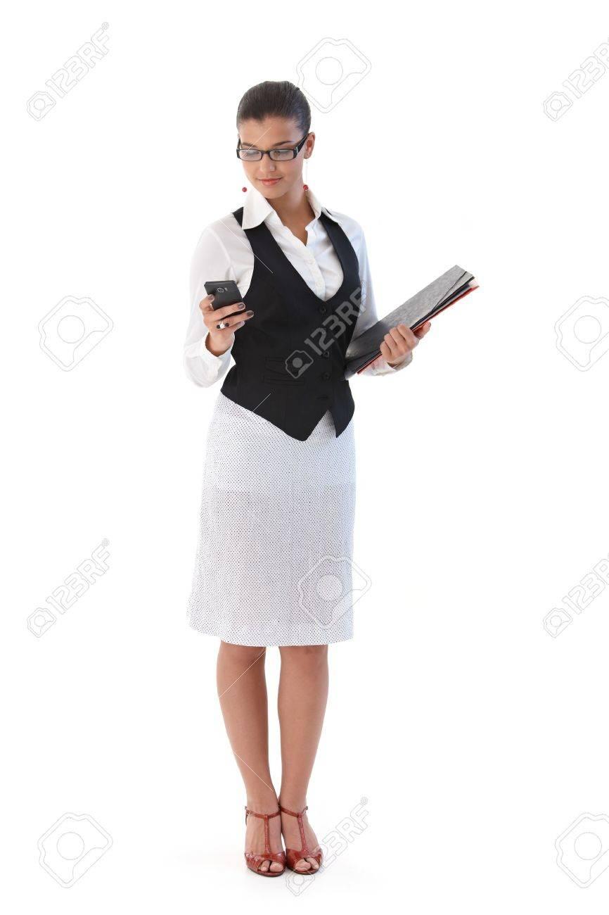 Pretty secretary holding folders, using mobile phone. Stock Photo - 9712063
