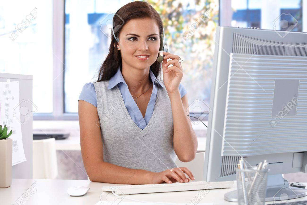 young customer service operator working in bright office sitting stock photo young customer service operator working in bright office sitting at desk smiling