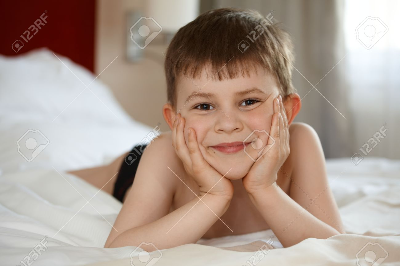 Cute little kid laying on bed, smiling, looking at camera Stock Photo - 9868548