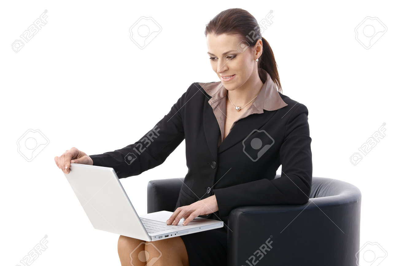 Businesswoman using laptop computer, sitting in armchair, looking at screen, smiling. Stock Photo - 9868500