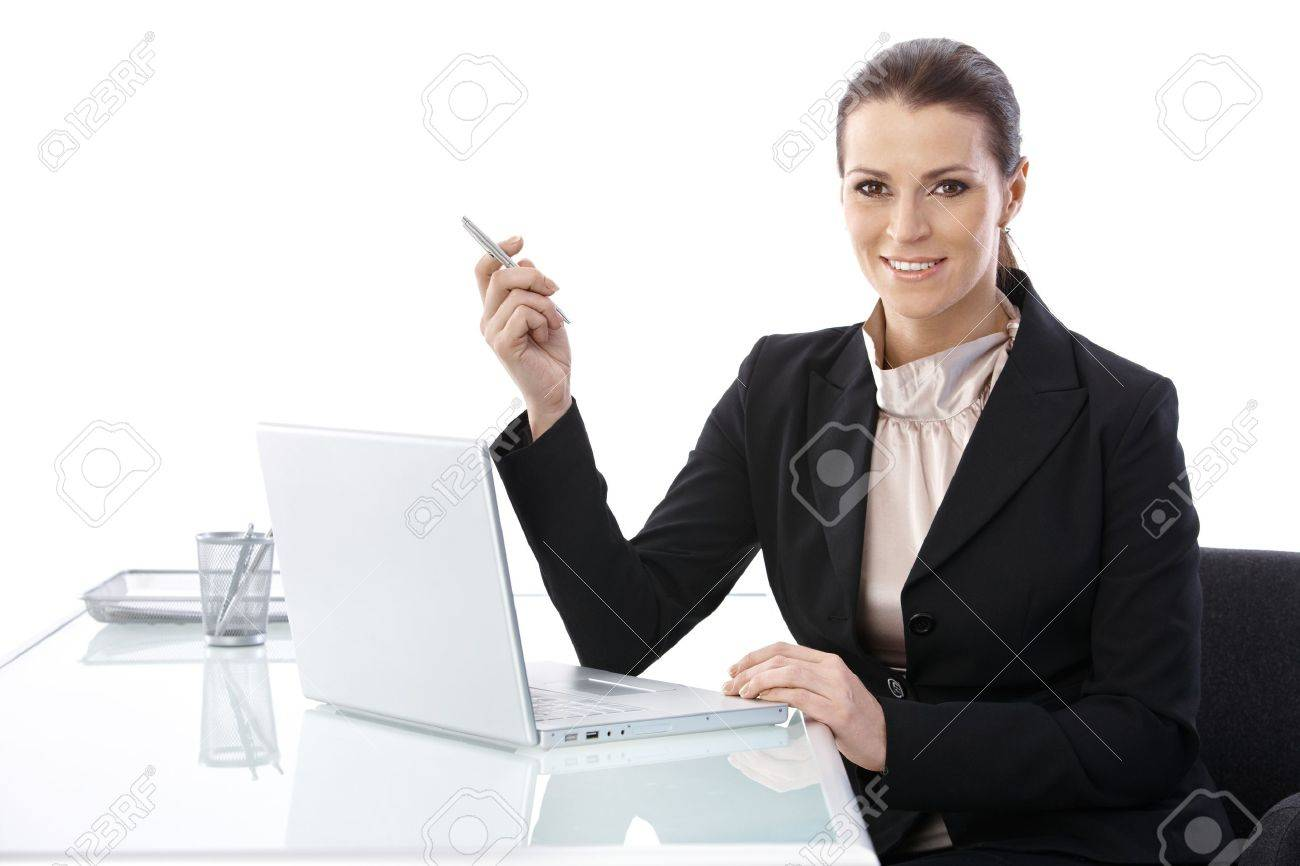 Mid-adult elegant businesswoman sitting at desk, using laptop computer holding pen, smiling at camera. Stock Photo - 9868523