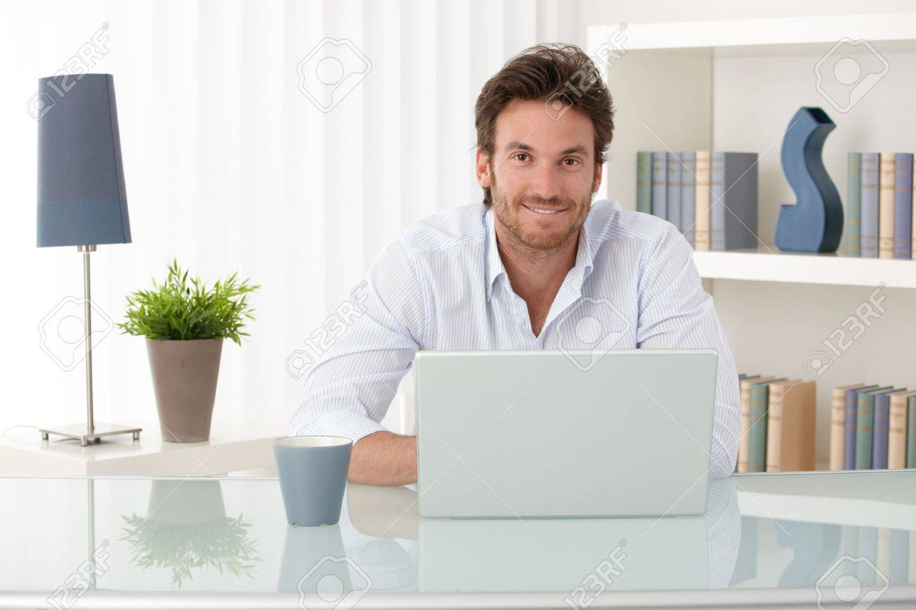 Portrait of goodlooking man sitting at table at home with laptop computer, smiling at camera. Stock Photo - 10373318