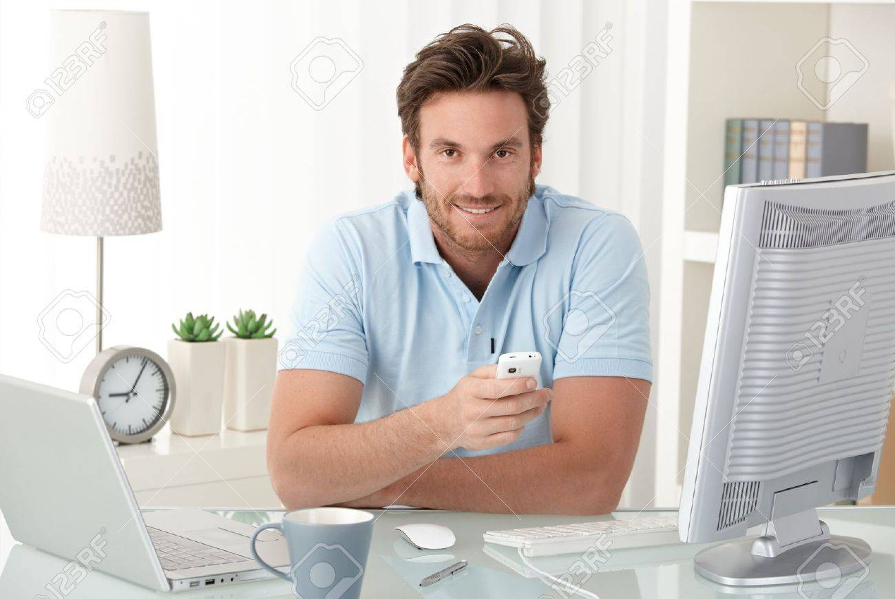 Smiling man at desk with mobile phone handheld, looking at camera, having computer. Stock Photo - 10373329