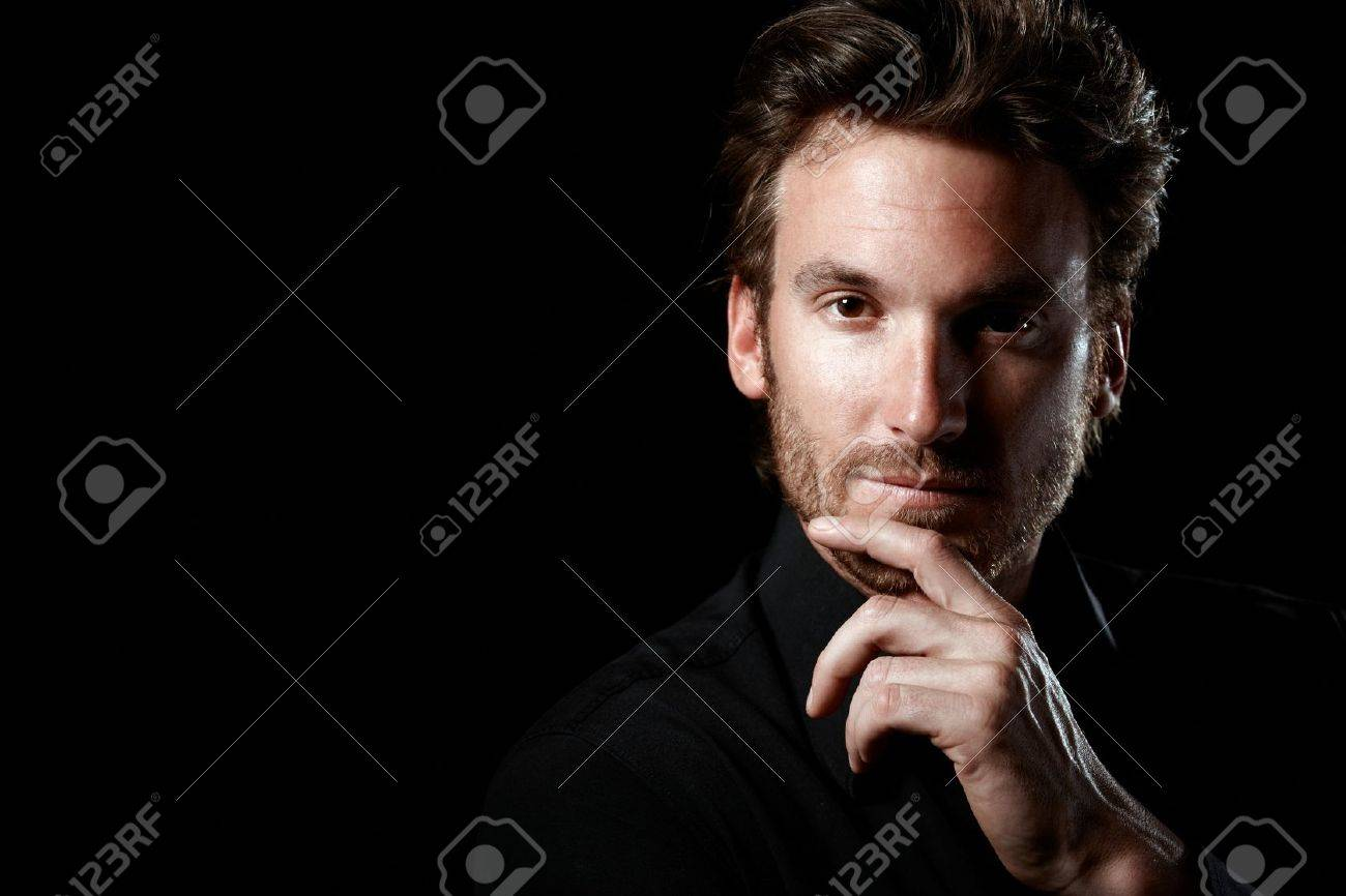 Closeup portrait of confident man thinking, wearing black, looking at camera, black background. Stock Photo - 10373317