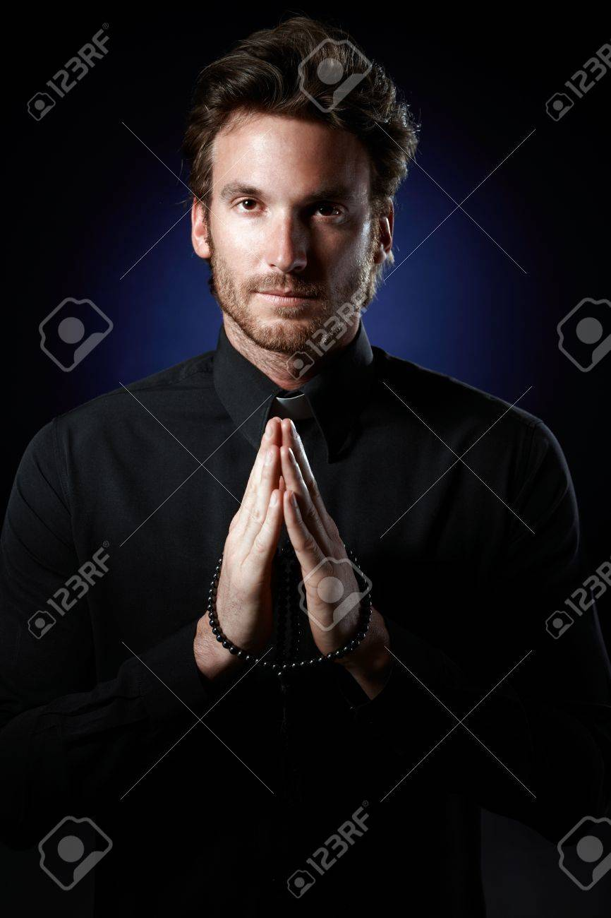 Priest praying with rosary, looking at camera. Stock Photo - 10373332