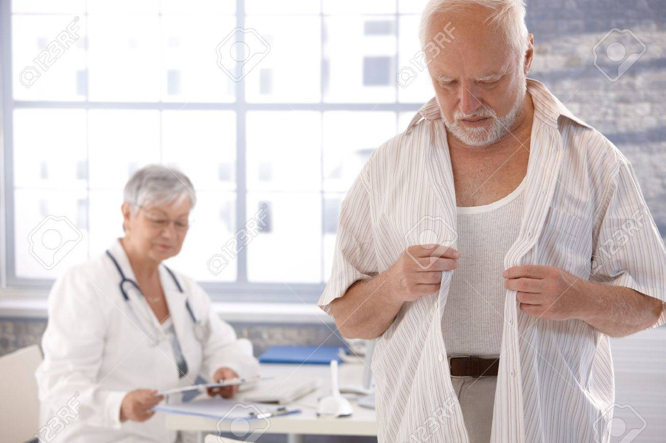mature male patient undressing at doctor's room. stock photo