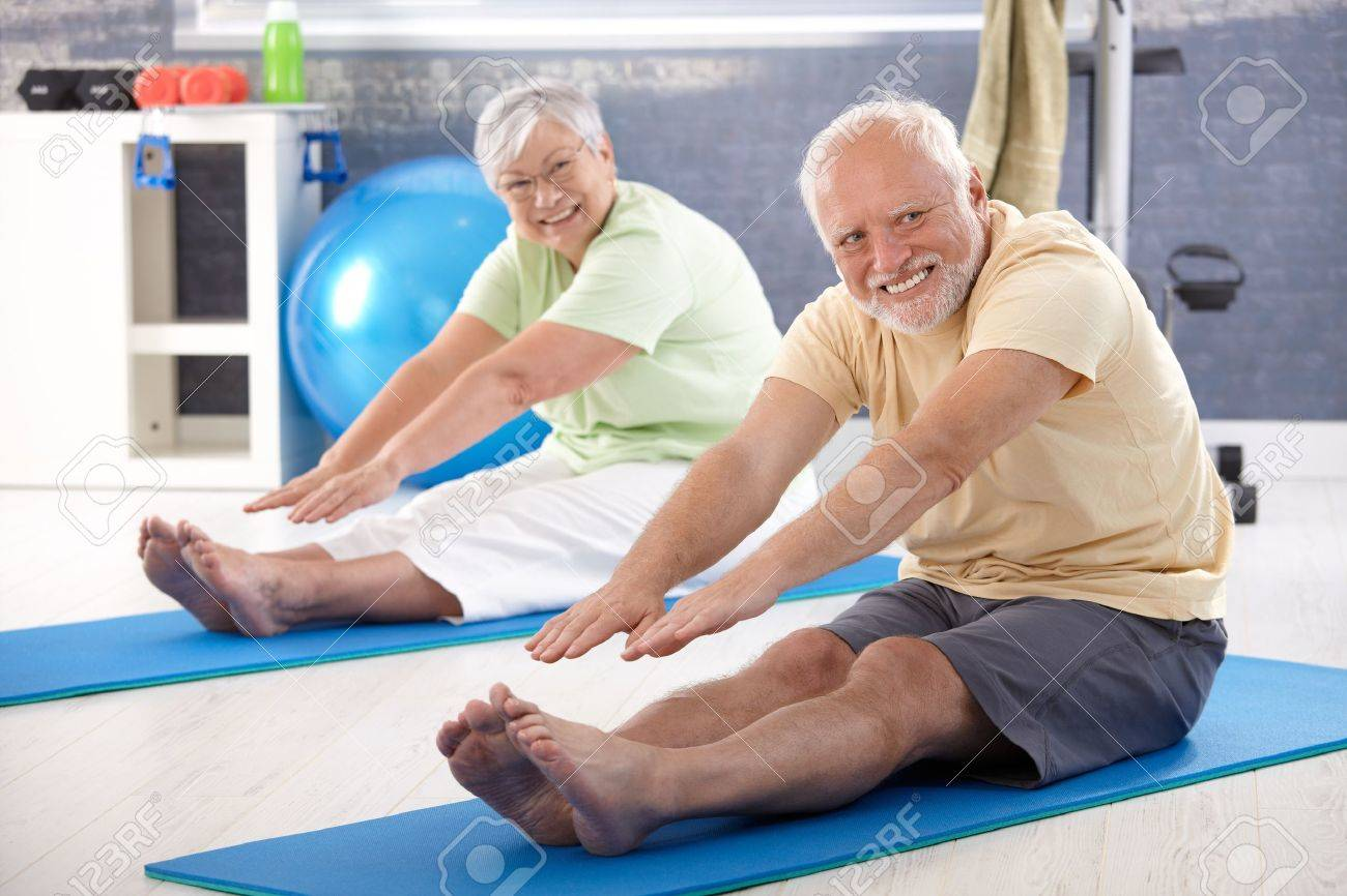 Elderly couple stretching in the gym. Stock Photo - 10373378