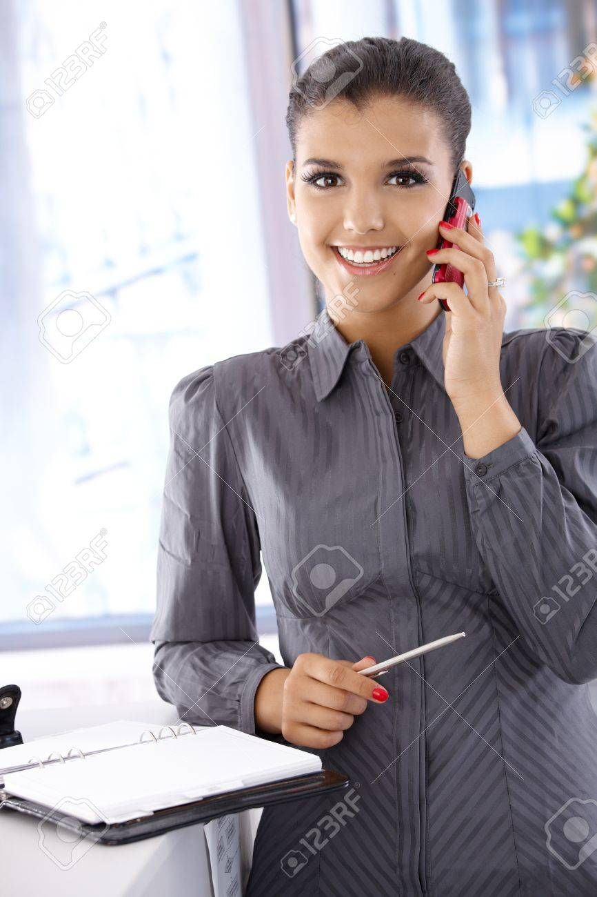 Beautiful businesswoman talking on mobile phone, smiling, looking at camera. Stock Photo - 10377643