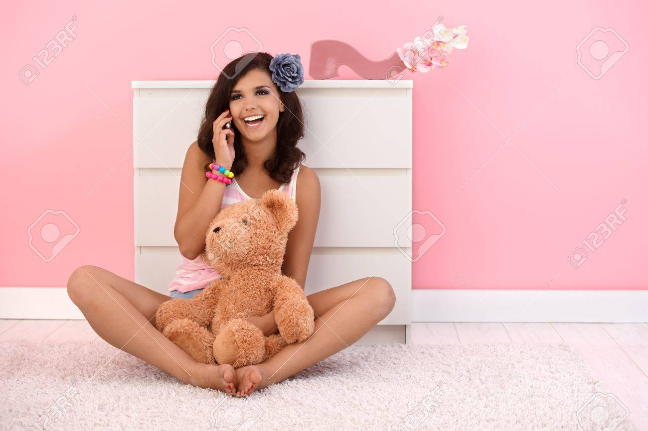 Beautiful girl sitting on floor with teddy bear, talking on mobile phone. Stock Photo - 10377600