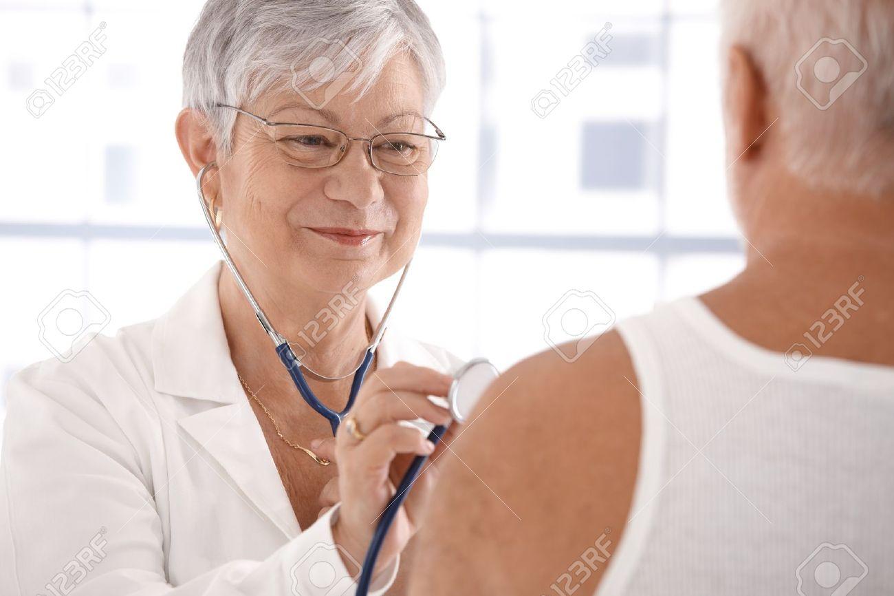 Senior female doctor examining male patient, smiling. Stock Photo - 10389951