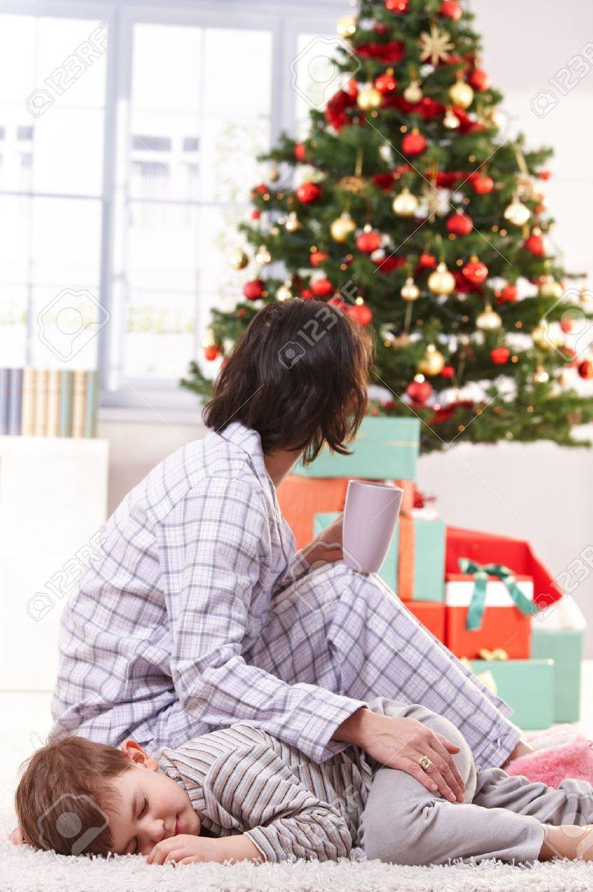 Mother stroking sleeping son on christmas morning, looking at tree and wrapped gifts, having tea. Stock Photo - 10533292