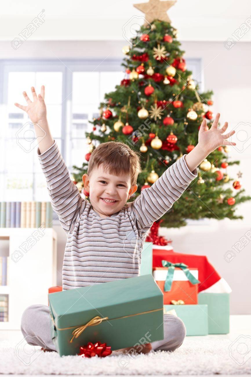 Happy Kid Sitting In Pyjama On Christmas Morning, Raising Arms ...
