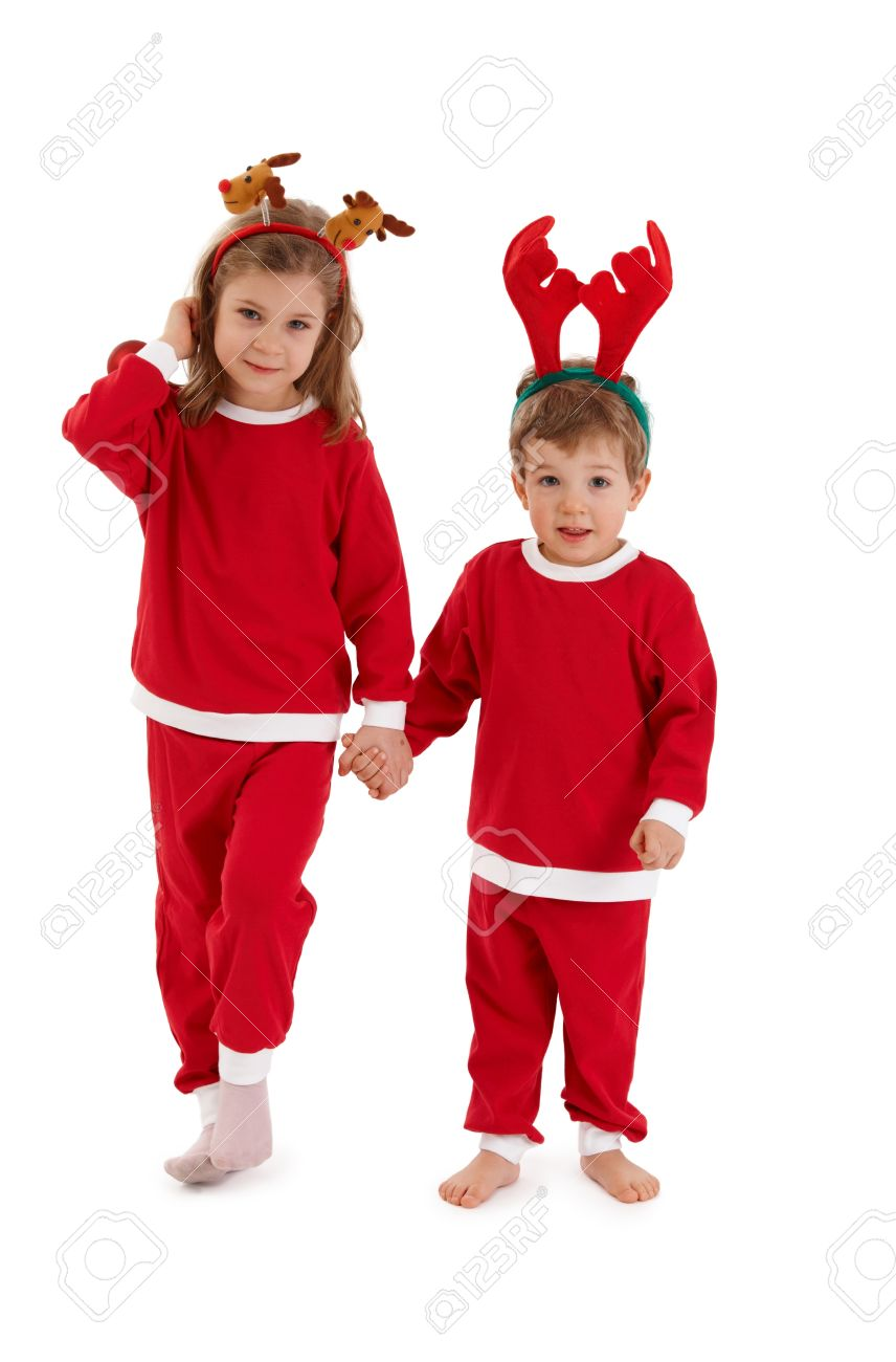 Christmas portrait of cute siblings wearing reindeer hair band and santa costume, holding hands. Stock Photo - 10663503