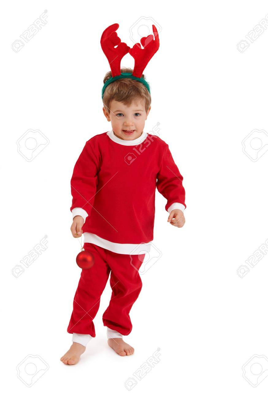 Little boy in reindeer hair band wearing santa costume playing with christmas bulb. Stock Photo - 10663478