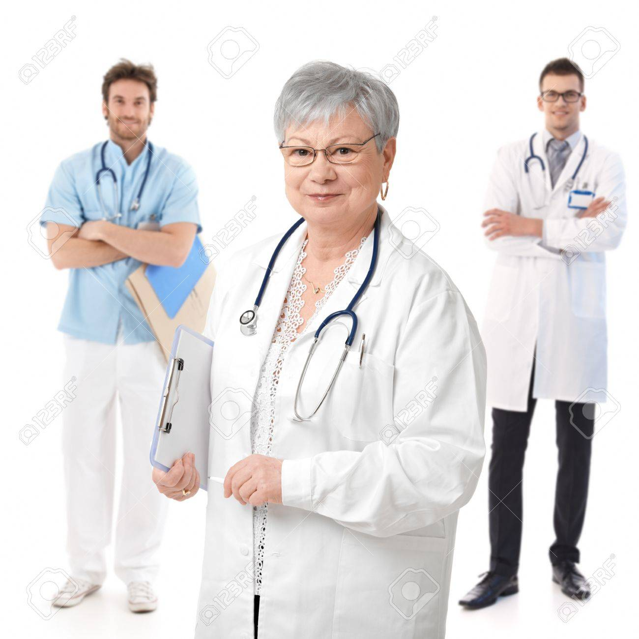 Portrait of experienced female doctor smiling, young male doctors standing behind. Stock Photo - 10818451