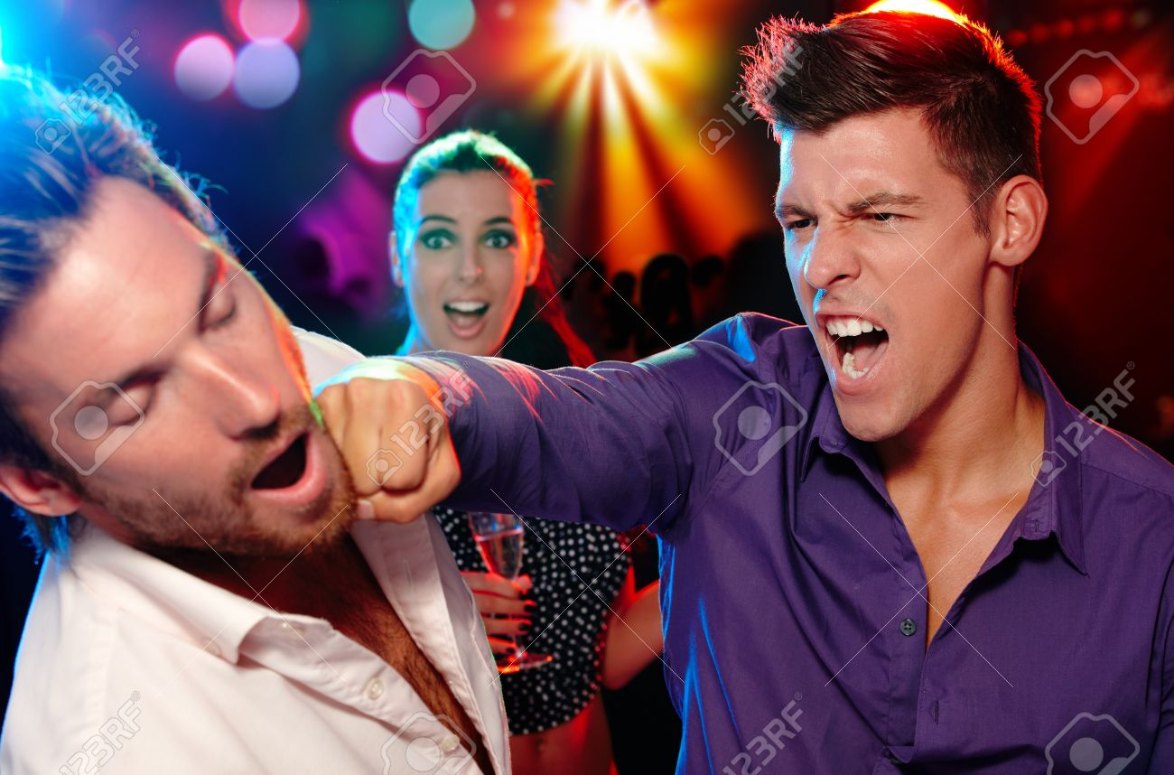 One man hitting another on the face in nightclub, woman watching from background. Stock Photo - 11157149