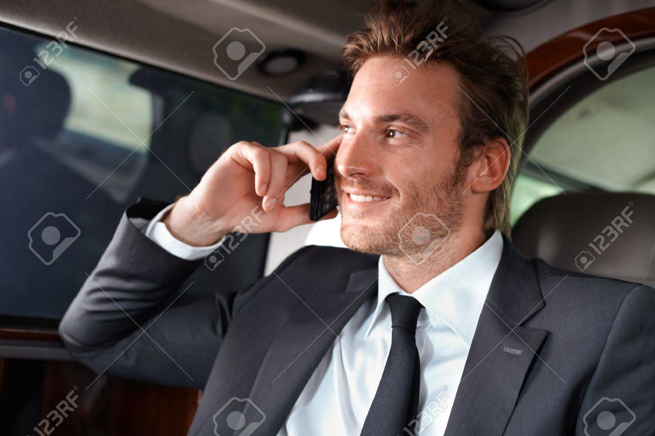 Elegant businessman traveling in luxury car, talking on mobile phone, smiling. Stock Photo - 12063376