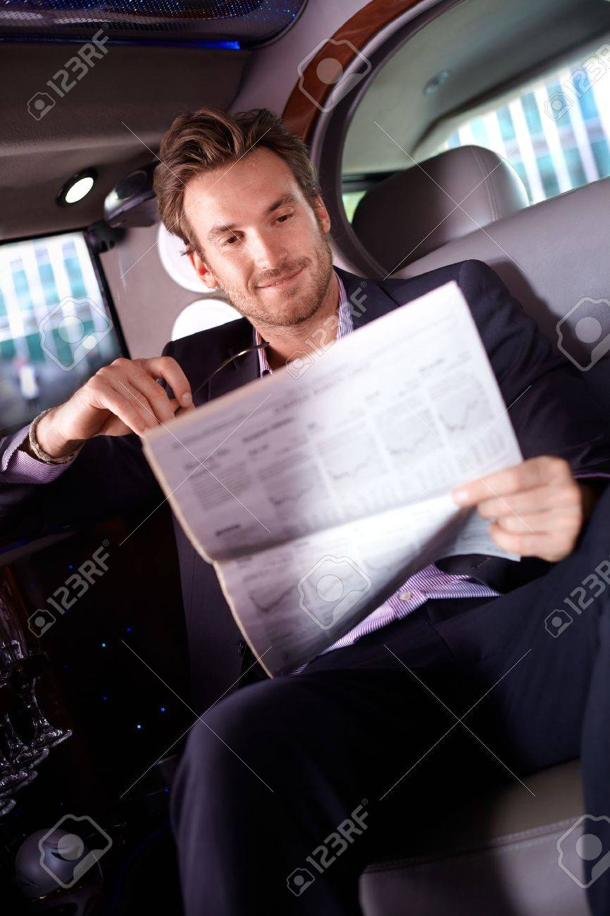 Smart young man reading newspaper in limousine, smiling. Stock Photo - 12070902