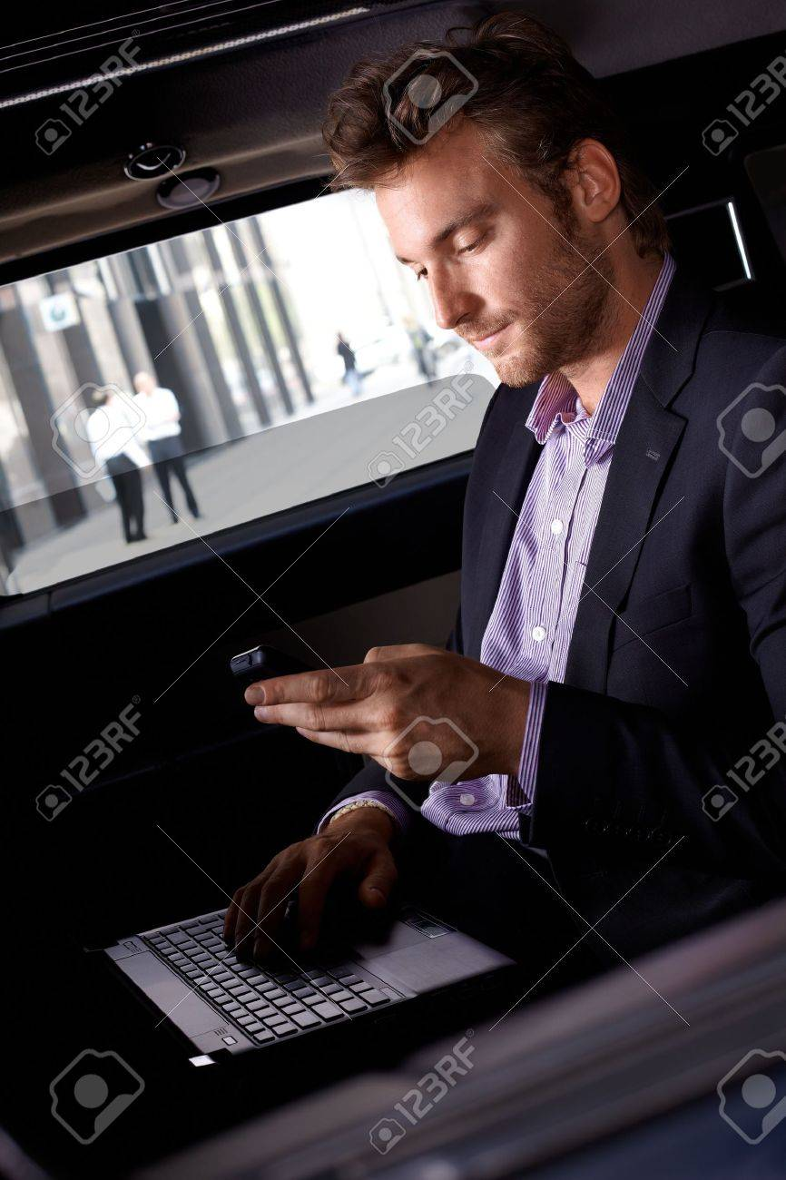 Smart young businessman using laptop and mobile in luxury automobile, working. Stock Photo - 12063319