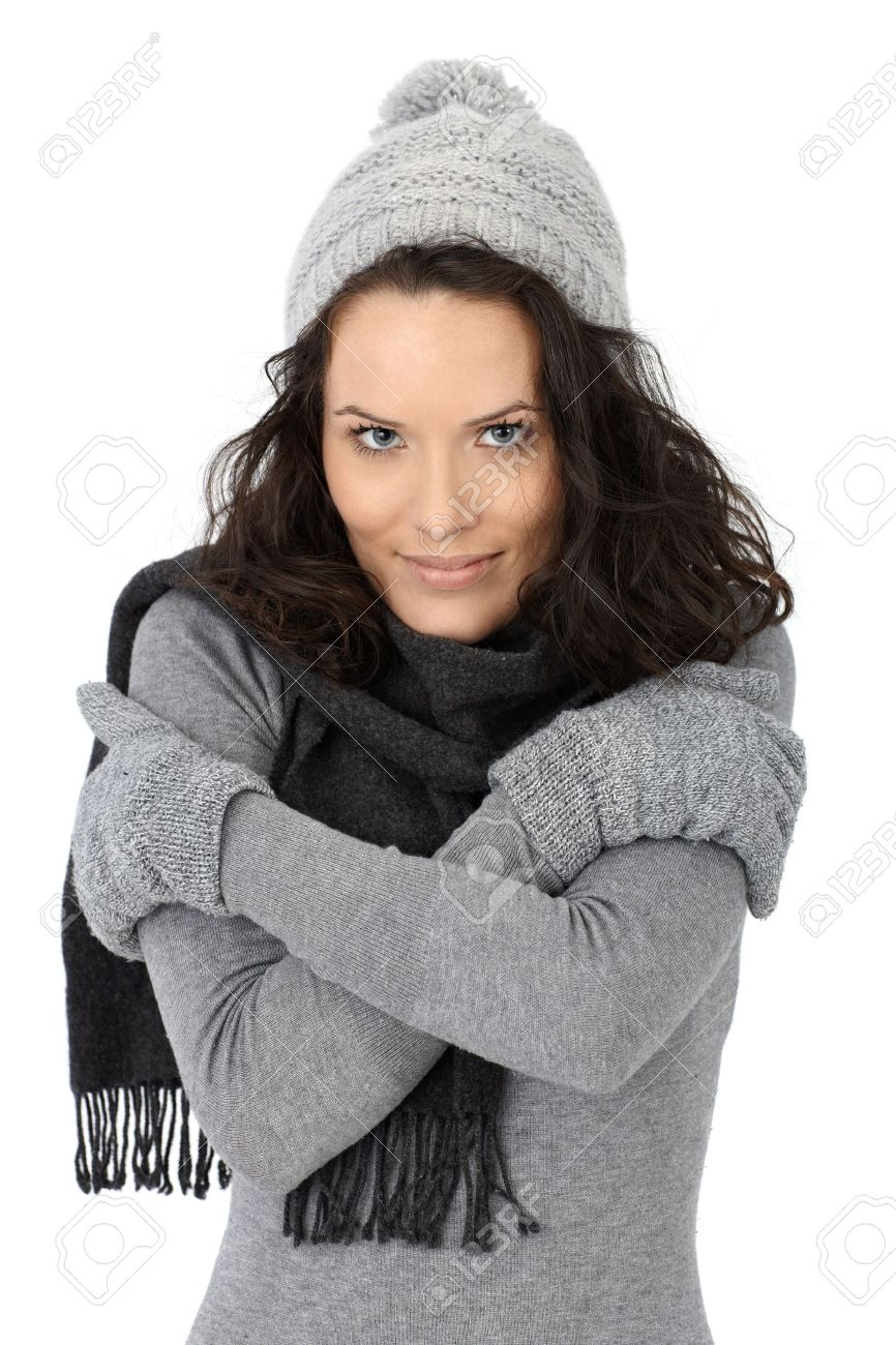 Beautiful woman feeling cold in winter, wearing scarf cap and gloves, isolated on white. Stock Photo - 12174639