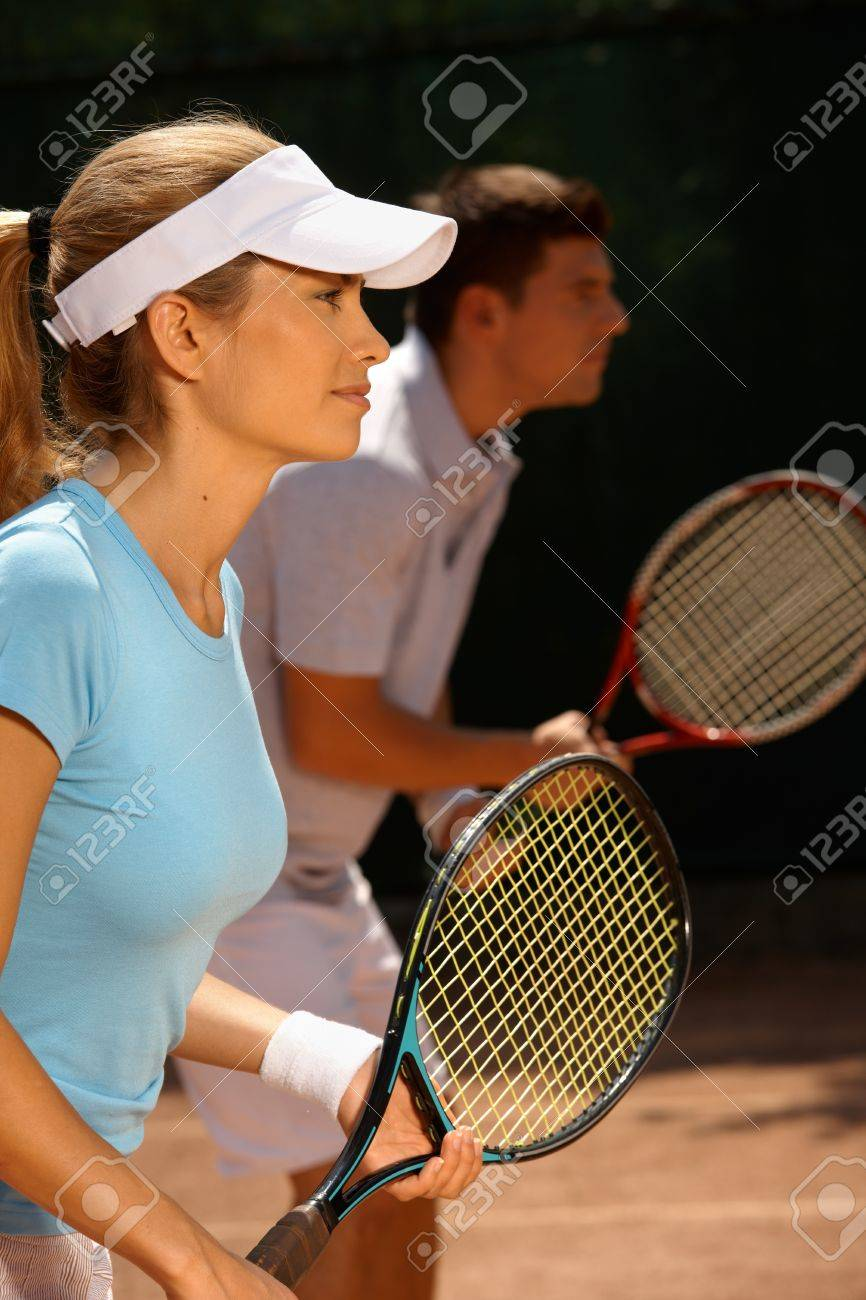 Young people playing tennis, mixed doubles, side view. Stock Photo - 12174724