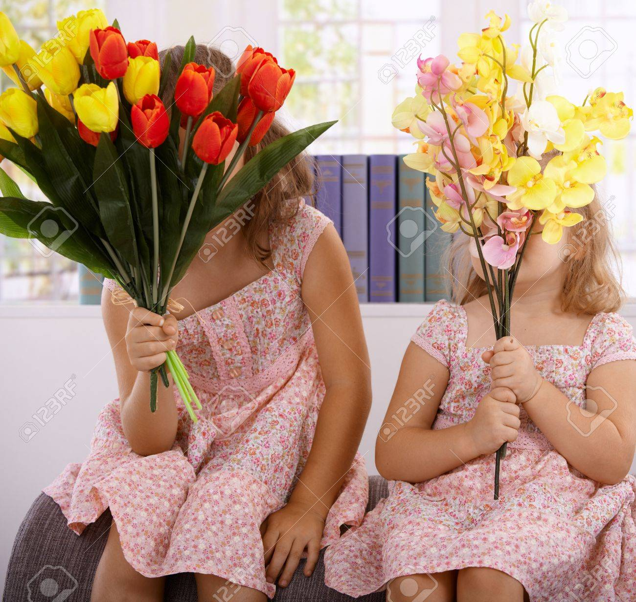 Little girls hiding behind bouquet of flowers at mother's day. Stock Photo - 12471029