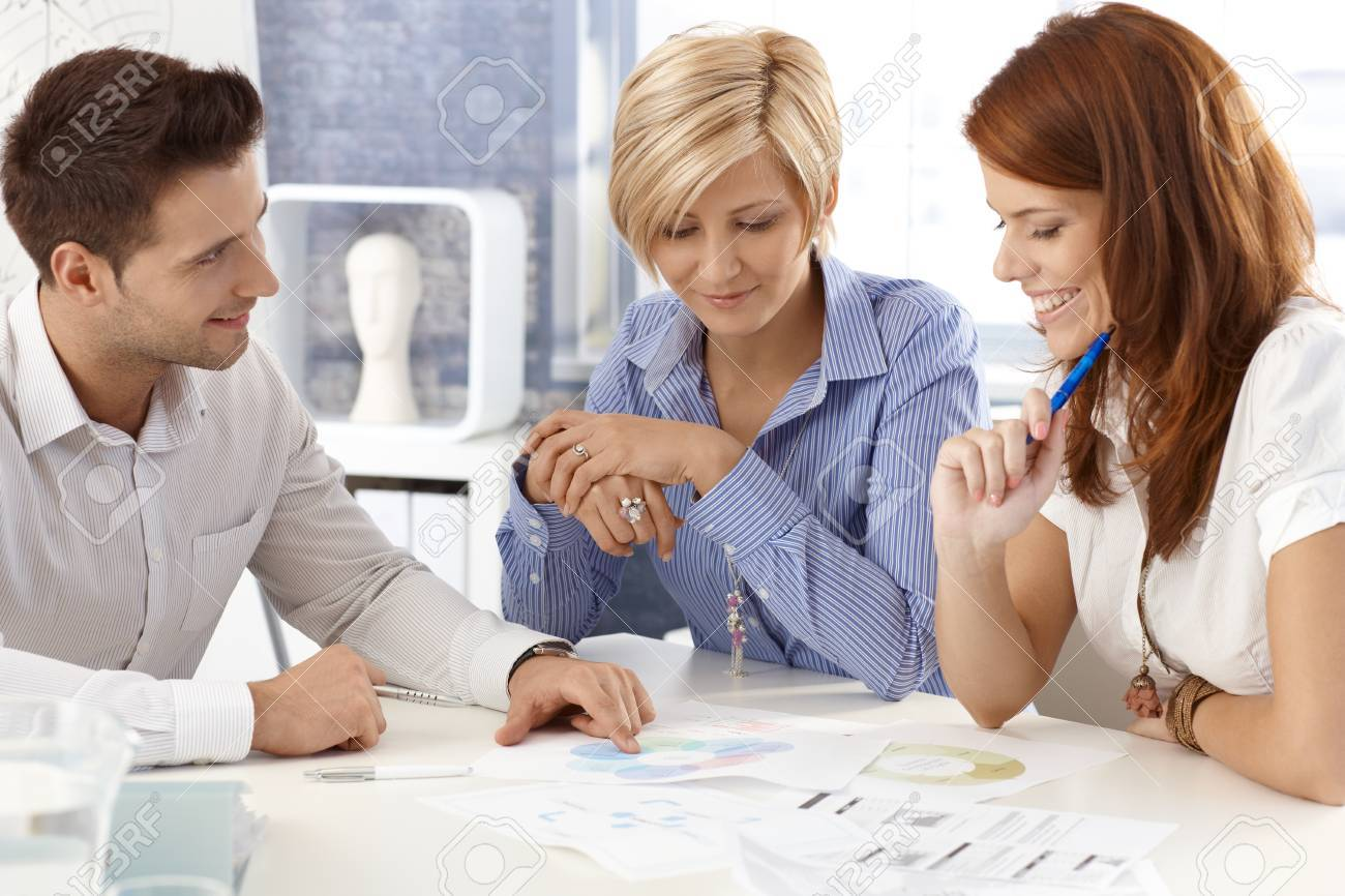 Portrait of happy businessteam working together a meeting table, businessman explaining, pointing at documents. - 12472059