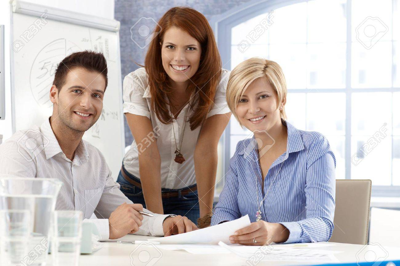Portrait of happy and attractive office team, smiling at camera. - 12471876